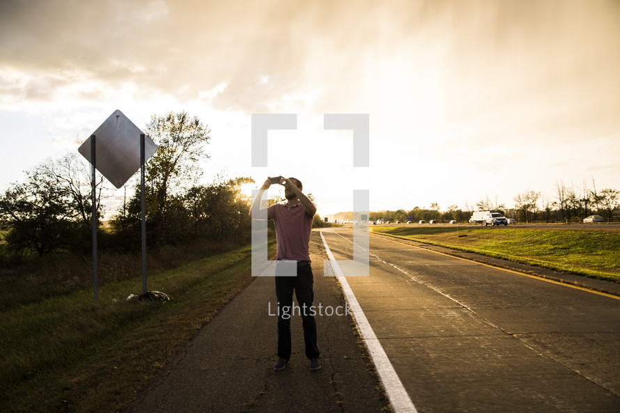 man taking pictures on the side of a road