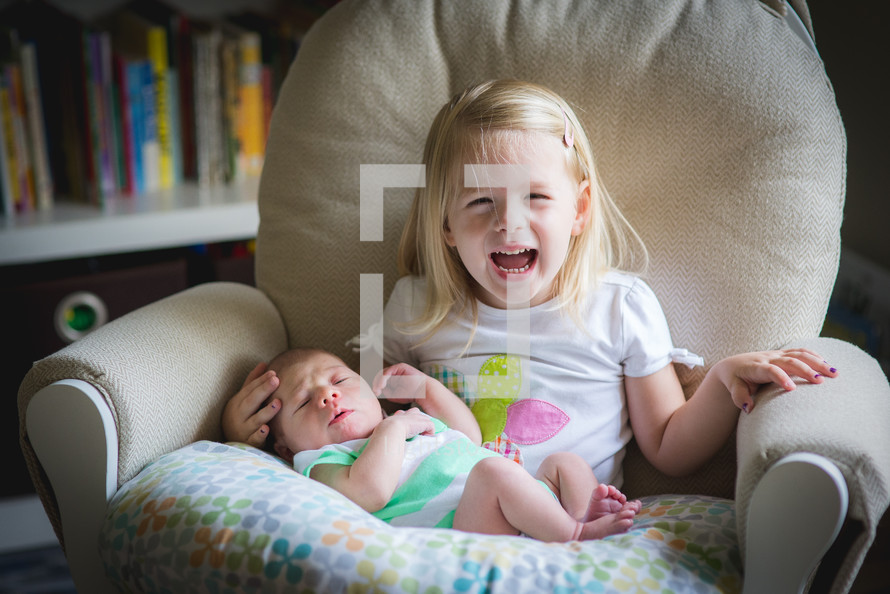 a girl holding her baby brother