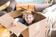 toddler hiding in a cardboard box