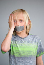 a boy child with duct tape over his mouth