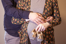 expecting couple holding infant shoes