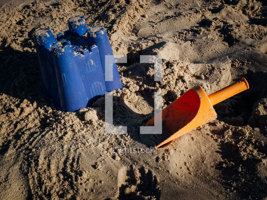 a children's trowel shovel and sandcastle bucket on the beach