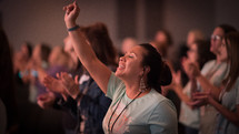 a woman at a worship service with hand raised