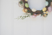 an Easter wreath hanging on a door