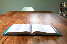 Open Bible on a big wood table in a dining room