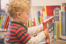 toddler boy picking out books at the library