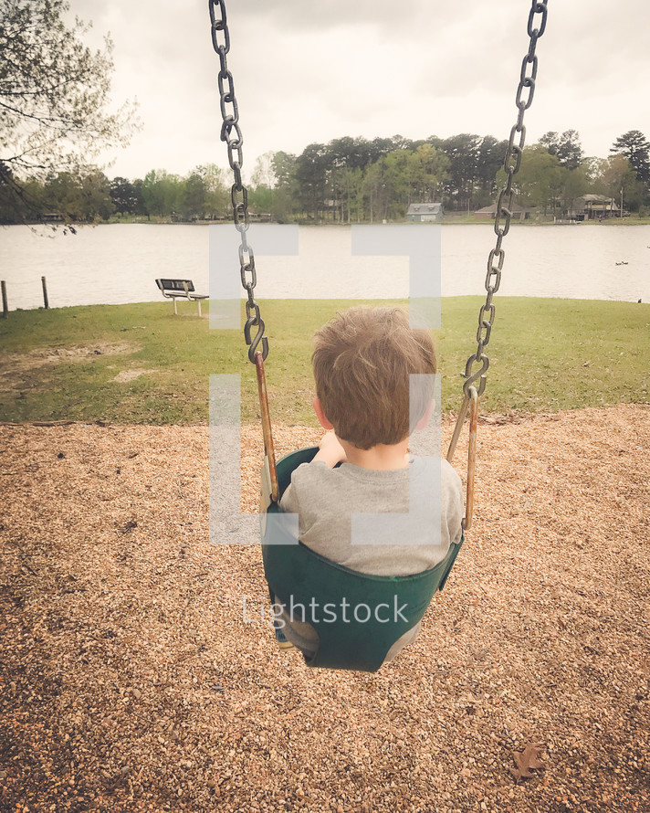toddler boy on a swing at a park