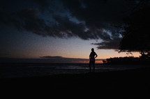 silhouette of a man standing on a beach