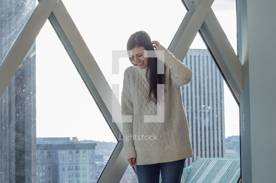 a young woman standing in a window with city view behind her