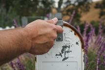 man opening a rusty mailbox
