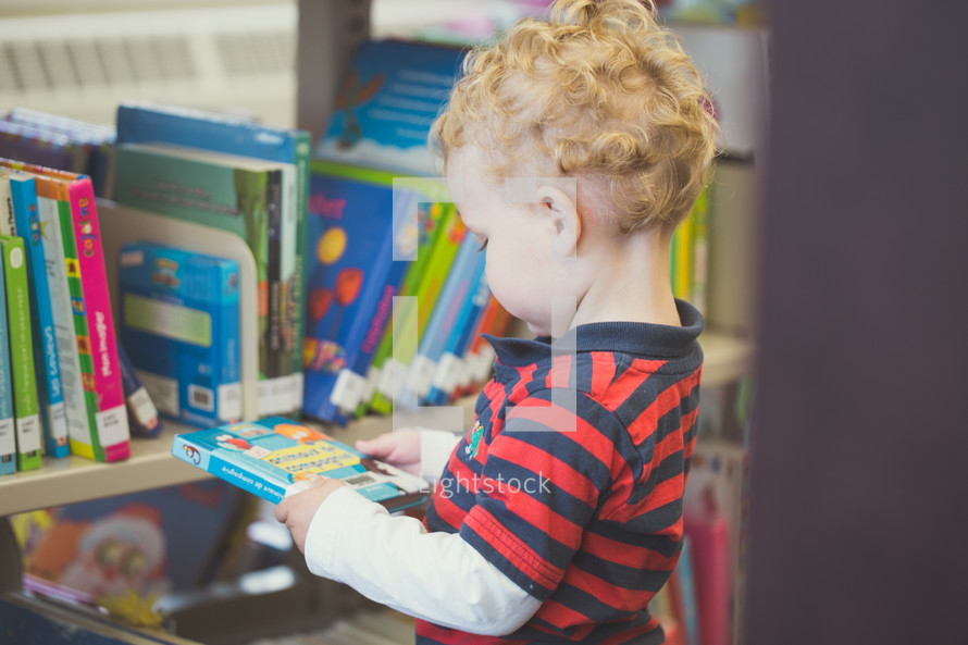 a toddler boy picking out books at the library