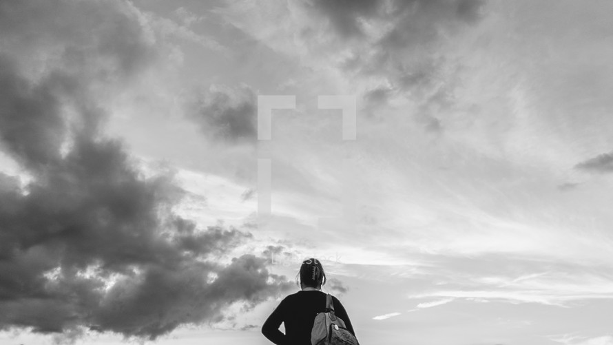 a woman with a backpack looking up at the sky