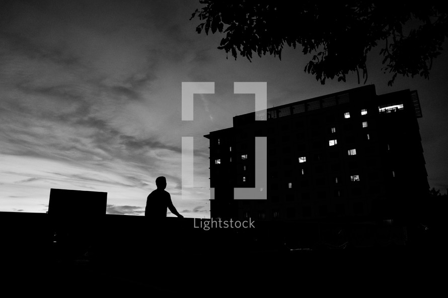 silhouette of a man and a building at night