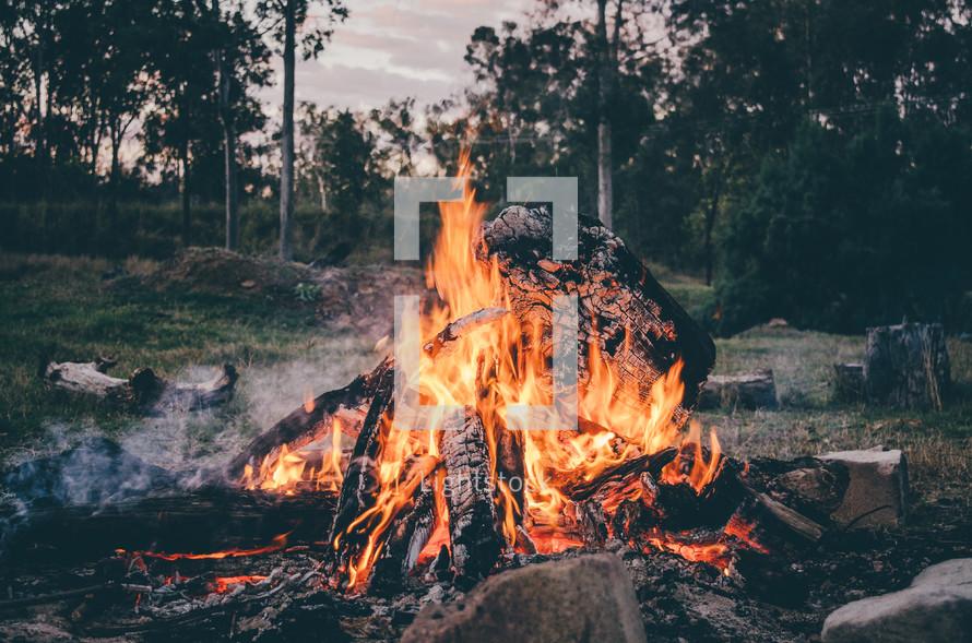 a campfire burning at dusk