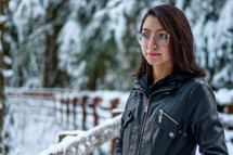 a young woman standing outdoors in snow