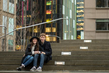 a couple sitting on concrete steps outdoors