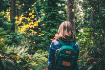 a girl with a backpack walking into the woods