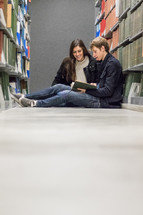 a couple reading on a library floor