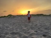 a little boy running in the sand on a beach