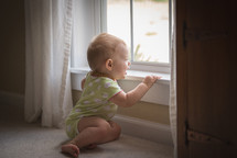 infant in a onesie looking out a window