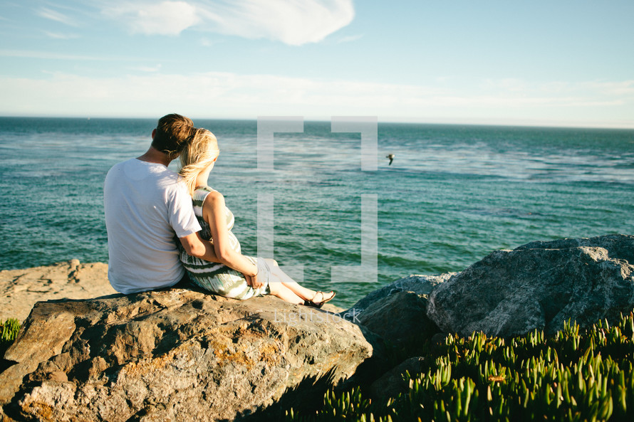 couple sitting on rocks near a beach looking out at the ocean