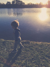 a toddler boy walking on a shore by a pond