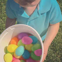 toddler boy holding a bucket of Easter eggs