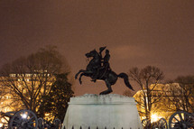 Bronze statue of Andrew Jackson on a horse, surrounded by cannons at night.