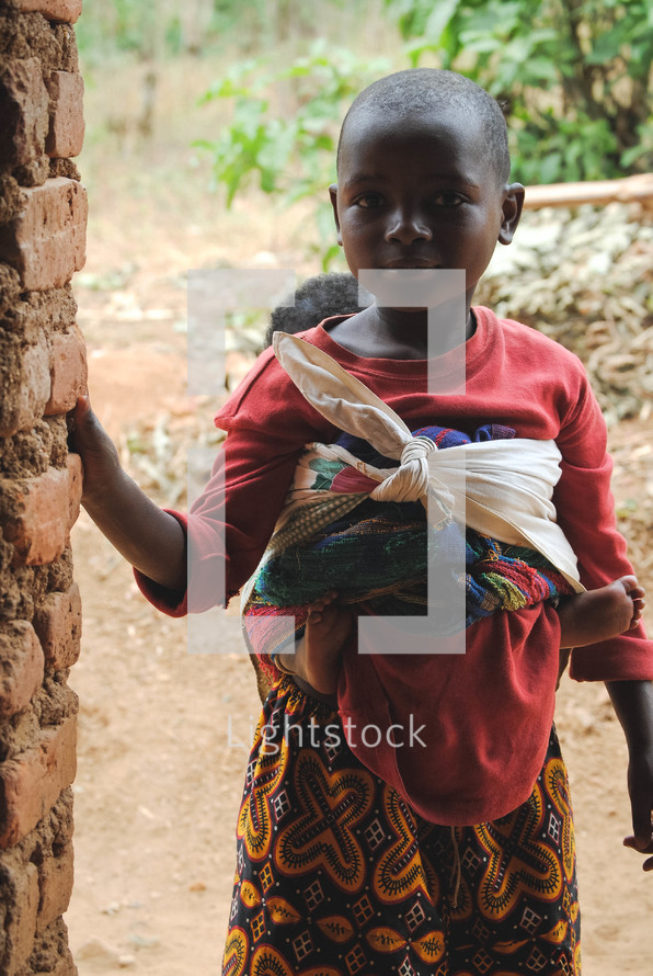 young girl with a papoose and baby in Rwanda