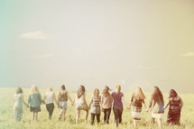 Teen girls holding hands, standing in a field.