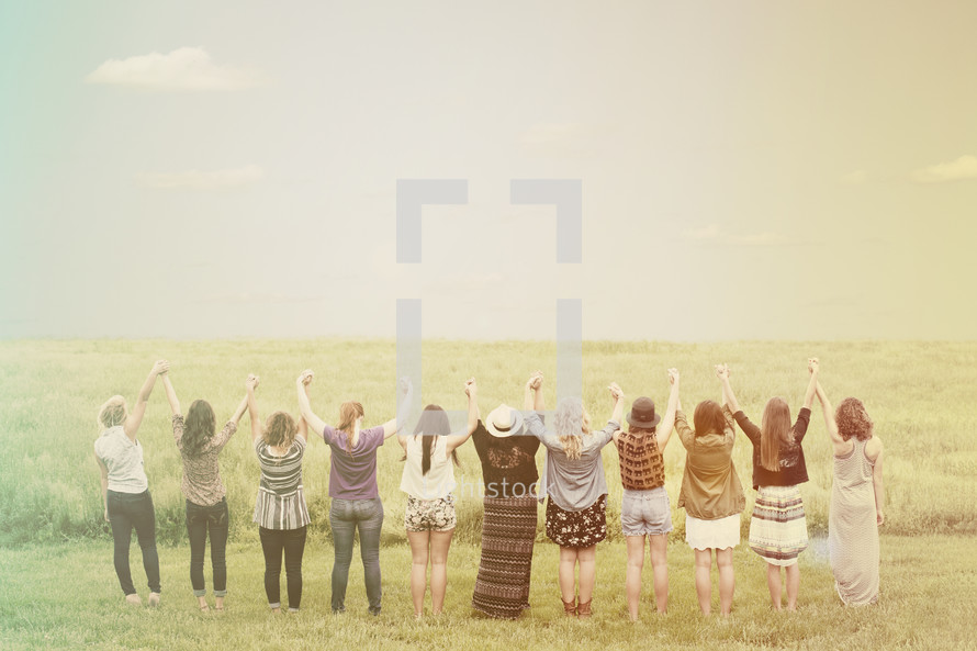 Teen girls standing in a field of grass holding hands with arms raised.
