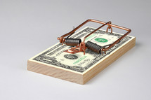 mouse trap on a stack of dollars