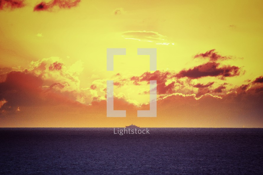 distant ship on the water under a yellow sky at sunset