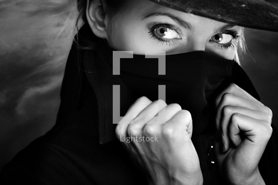 a woman hiding her face in a coat collar