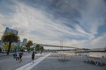 San Francisco Bay Bridge, palm trees, street lamps, runners, jogging, picnic benches