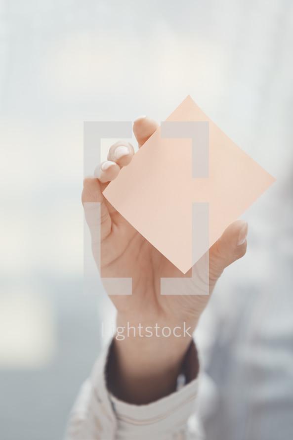 woman holding up a blank sticky note