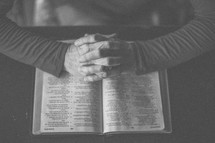 A woman's hands folded in prayer over an open Bible
