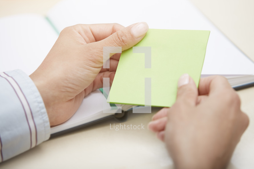 woman holding a blank sticky pad