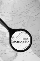 magnifying glass over a map of Afghanistan