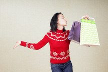 a woman in a red sweater with shopping bags