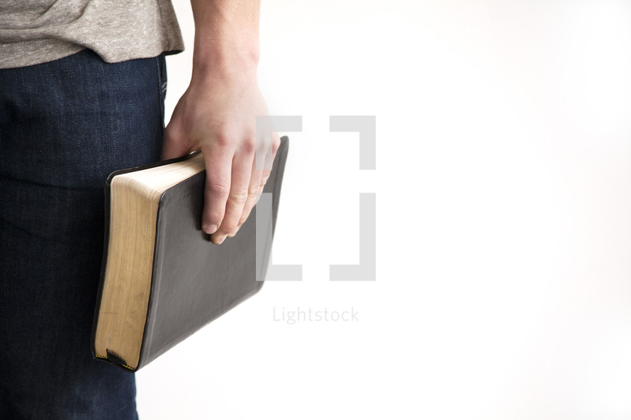a man holding a Bible at his side