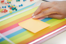 a woman with a blank sticky note on her desk