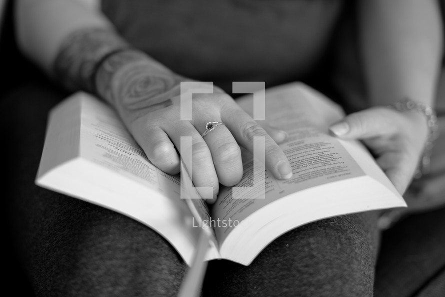 a person with tattoos reading a Bible