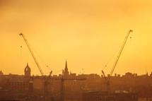 construction cranes in a city under an orange sky