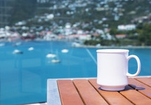 coffee mug on a table and view of boats in a bay