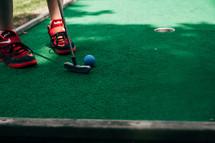 a boy playing putt putt
