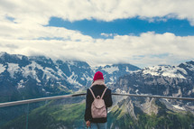 a woman looking out at a snowy mountain