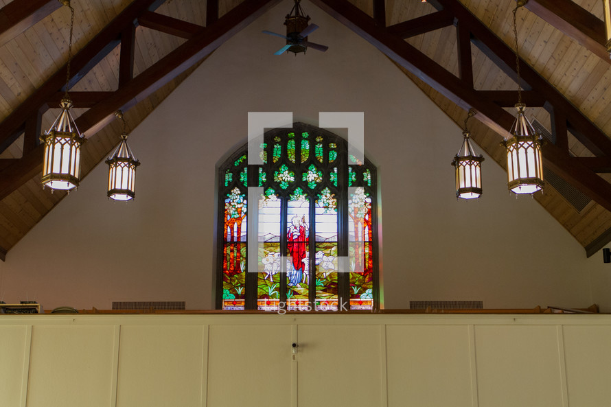 stained glass window and hanging lights in a church