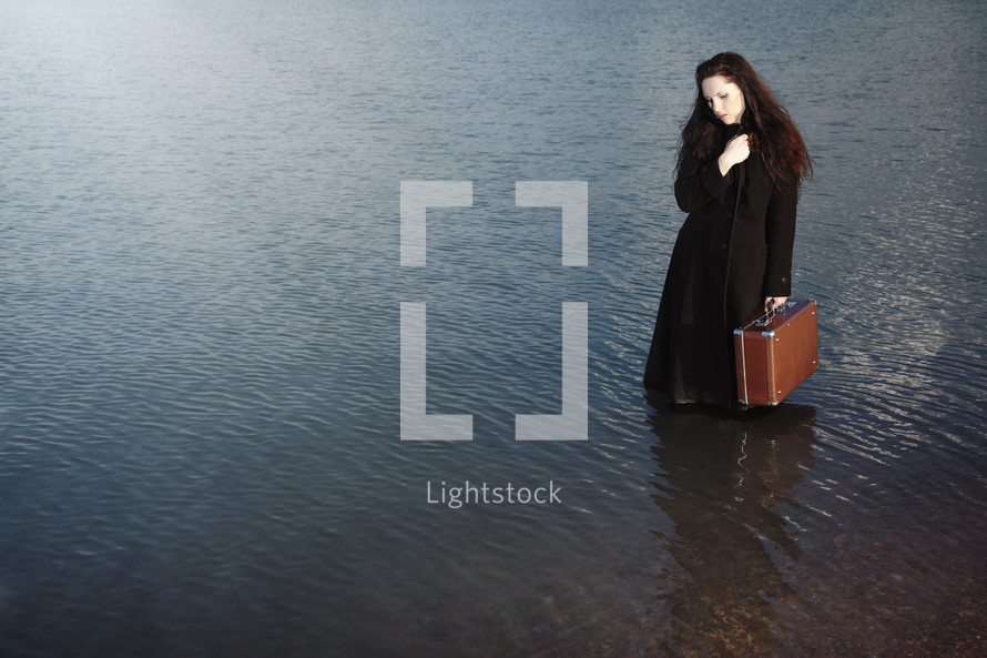 a woman holding a suitcase standing in water