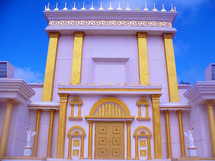 A replica of an Ancient Jewish Temple  with gold pillars, doors and columns against a stone white and marble building  against a light blue sky just like the Jewish temples of old during ancient bible times.